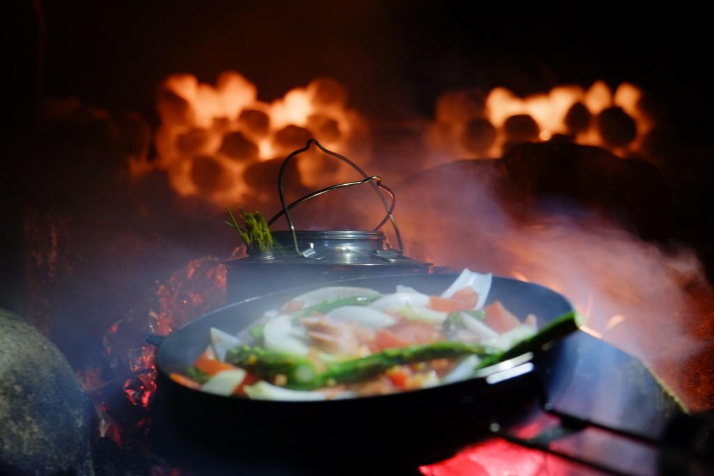 Snølyktene og bålet gjør det stemningsfullt når middagen tilberedes.