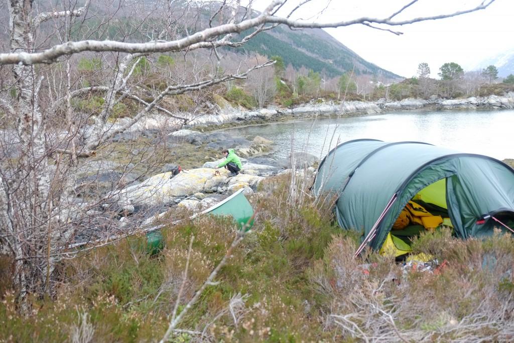 Teltet settes opp over tuer og lyng nede ved vannkanten.