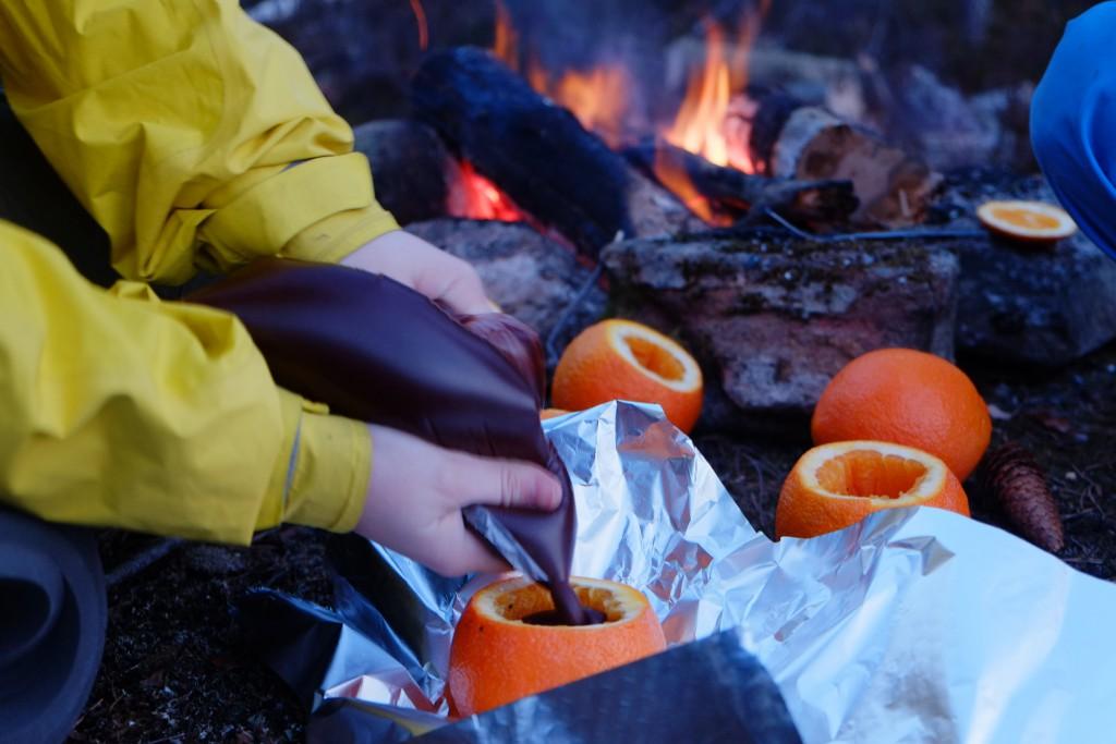 Flytende sjokolade fylles i appelsinene som legges i aluminiumsfolie på bålet